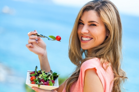 eating up: Portrait of beautiful young woman holding green salad outdoors at seaside.
