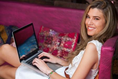 Retrato de la muchacha rubia linda que se relaja con la computadora portátil en el sofá.