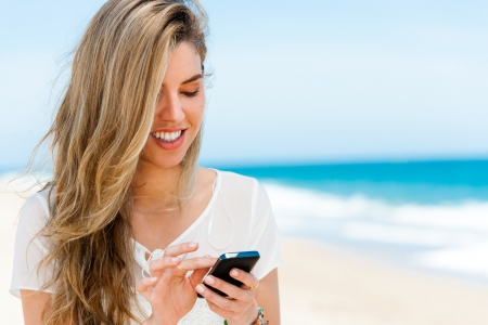 Portrait of attractive blond navigating with mobile phone on beach. photo