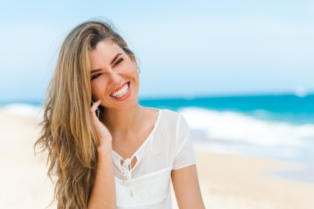 Portrait of cute girl talking on cell phone on beach. photo