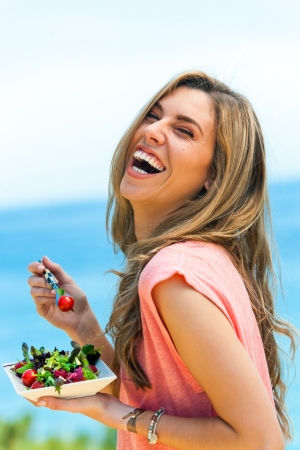 beautiful salad: Portrait of laughing girl with green salad at seaside.