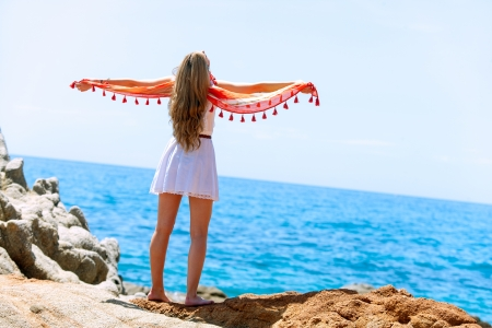 giving back: Young woman with colorful shawl giving back at seaside.