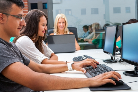 computer lab: Group of young students doing training course on computers. Stock Photo