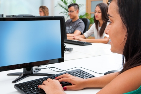 Young female student typing on computer keyboard in classroom. Stock Photo