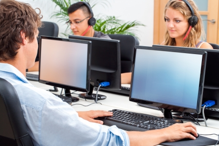 Group of students working on computers in classroom.