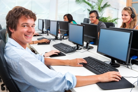 office workers: Portrait of smiling male student working on computer with mates. Stock Photo