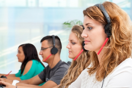 tele: Young office workers with headsets giving customer service. Stock Photo