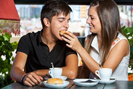 Close up portrait of teen couple fooling around in coffee bar. photo