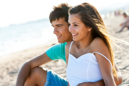 up to date: Cute teen couple sitting together on beach at sunset.