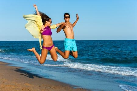 teen couple jumping high on sunny beach. photo