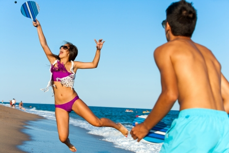 beach wear: Teen girl jumping at beach tennis ball.
