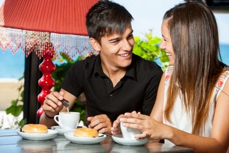 dining out: Close up portrait of teen couple enjoying breakfast in restaurant.