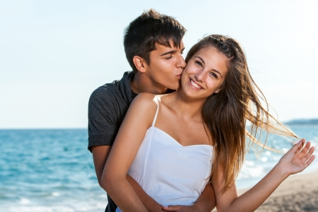 girls kissing: Close up portrait of teen couple embracing on beach. Stock Photo