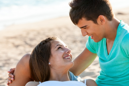 Close up portrait of teen couple sharing romantic moment on beach. photo