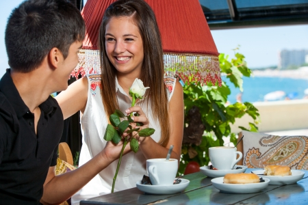 Young man giving flower to girl at coffee date. photo