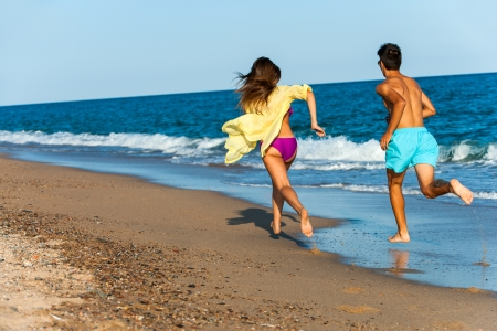 teen couple chasing each other on beach. photo