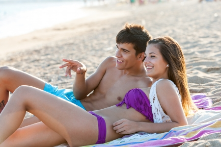 amorous woman: Portrait of teen couple enjoying late afternoon sun on beach. Stock Photo