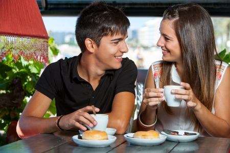 Close up of teen couple having coffee together. photo