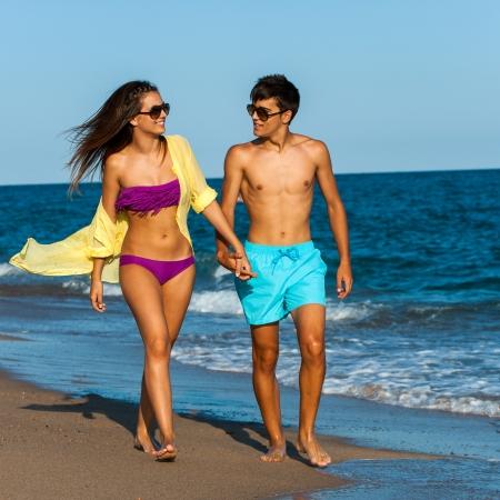 strolling: Teen couple in swim wear holding hands at seaside. Stock Photo