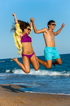 Dynamic teen couple in swim wear jumping on beach. photo