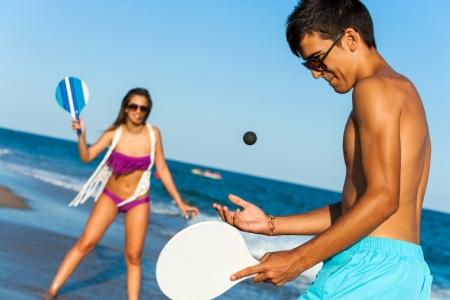 Teen couple in swim wear playing smash ball beach tennis outdoors. photo