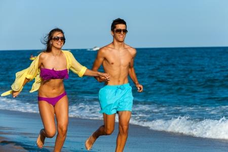 beach wear: Teen couple holding hands while running along beach.