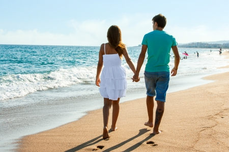 Rear view of Teen couple walking along beach in afternoon sun.  photo