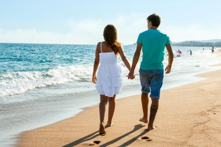 strolling: Rear view of Teen couple walking along beach in afternoon sun.