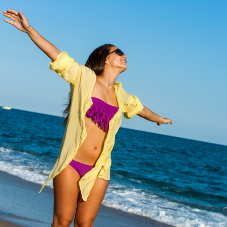 Portrait of teen girl standing with arms open on sunny beach. photo