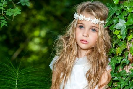Zblízka portrét roztomilé blond dívka v lese.