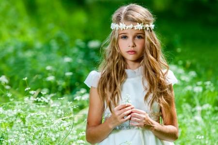 niña: Retrato de linda chica rubia vestida de blanco de pie en el campo verde.