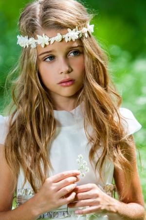 屋外の花を保持している白いドレスでかわいい女の子の肖像画を閉じます。 写真素材