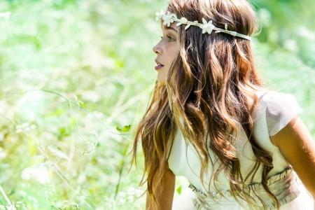 緑の野原でかわいい女の子の肖像画を閉じます。