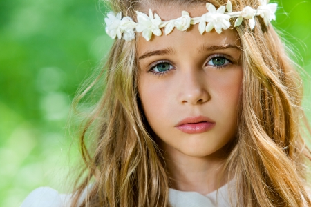 girl: Extreme close up of cute girl with flower headband outdoors. Stock Photo
