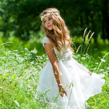 Cute girl holding white dress in green field. Stock Photo
