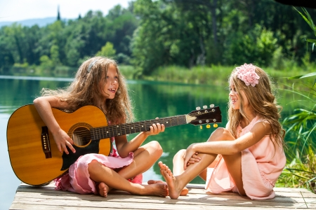 Portrait of two young girls singing together at lakeside. photo