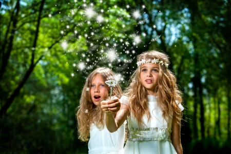 Fantasy portrait of cute girls with magic wand in forest. Stock Photo