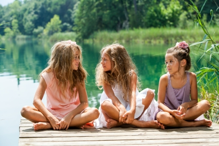 threesome: Portrait of young female threesome having conversation on river jetty. Stock Photo
