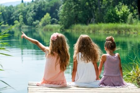 trio: Tres ni�os peque�os sentados juntos en el embarcadero en el lago.