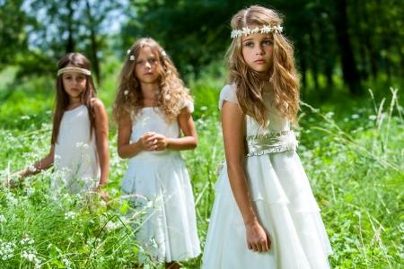 Portret van drie vriendinnen dragen witte jurken in bossen. Stockfoto