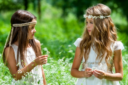 Close up portrait of two girls standing in flower field. Stock Photo