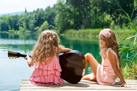 Young girls singing together with spanish guitar at lake. Stock Photo