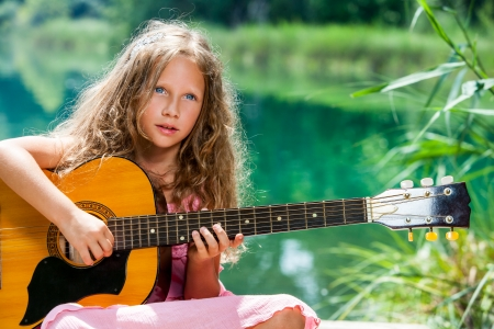 Close up portrait of young guitar student playing spanish guitar at lake. photo