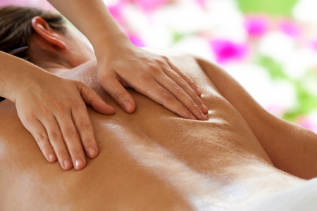 Close up of female therapists hands doing back massage on woman. photo