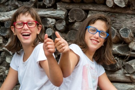 Portrait of two handicapped twin sisters doing thumbs up.