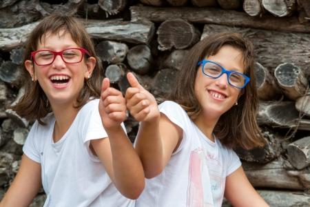 gemelas: Retrato de dos hermanas gemelas con discapacidad haciendo pulgares. Foto de archivo