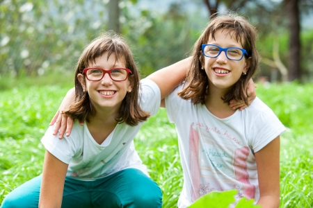 Portrait of two disabled twin sisters embracing outdoors. Stock Photo