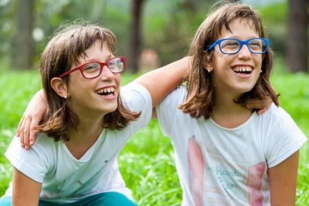 soeur jumelle: Close up portrait de deux soeurs jumelles handicap�es ext�rieur. Banque d'images