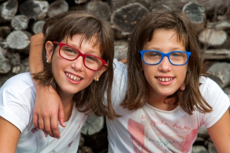 disadvantaged: Close up portrait of two disabled twin sisters smiling. Stock Photo
