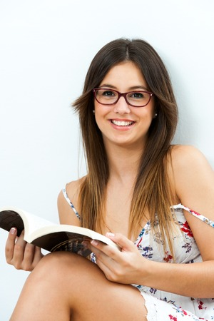 Cute teen girl sitting with novel at home. photo